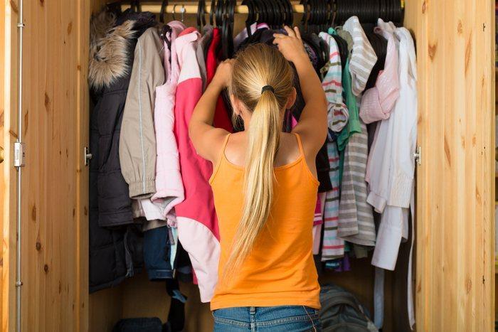 Девочка-подросткок выбирает себе одежду